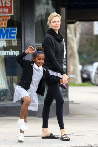Sherman Oaks, CA - *EXCLUSIVE* Charlize Theron enjoys a Menchie's frozen yogurt with daughter August Theron. The girls dance in the rain as they cross the street on the way back to their car after enjoying a cool treat together. Pictured: Charlize Therone BACKGRID USA 20 MARCH 2018 BYLINE MUST READ: EVGA / BACKGRID USA: +1 310 798 9111 / usasales@backgrid.com UK: +44 208 344 2007 / uksales@backgrid.com *UK Clients - Pictures Containing Children Please Pixelate Face Prior To Publication*